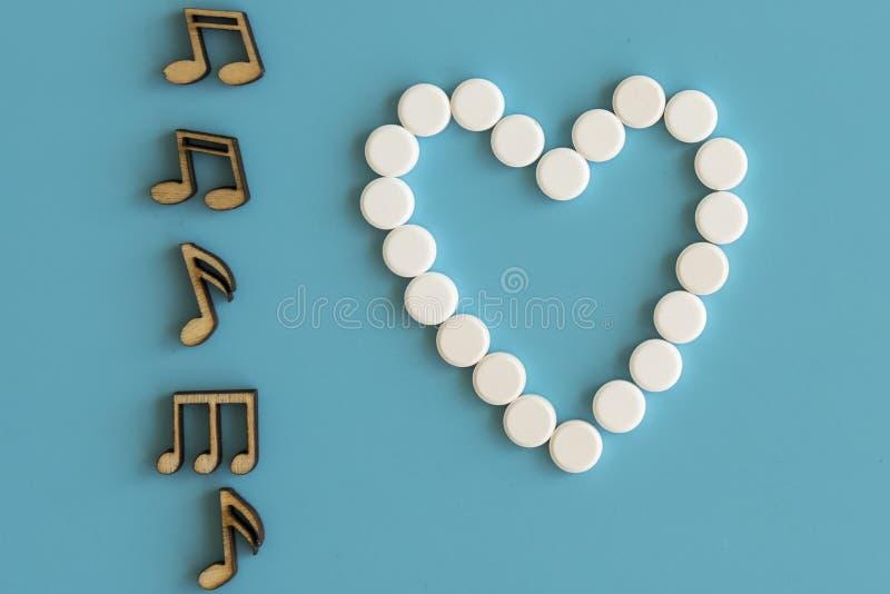 Het gezonde Concept van het Hart De hartwerken zoals een nota Muzieknota's en een hart op een blauwe achtergrond stock fotografie