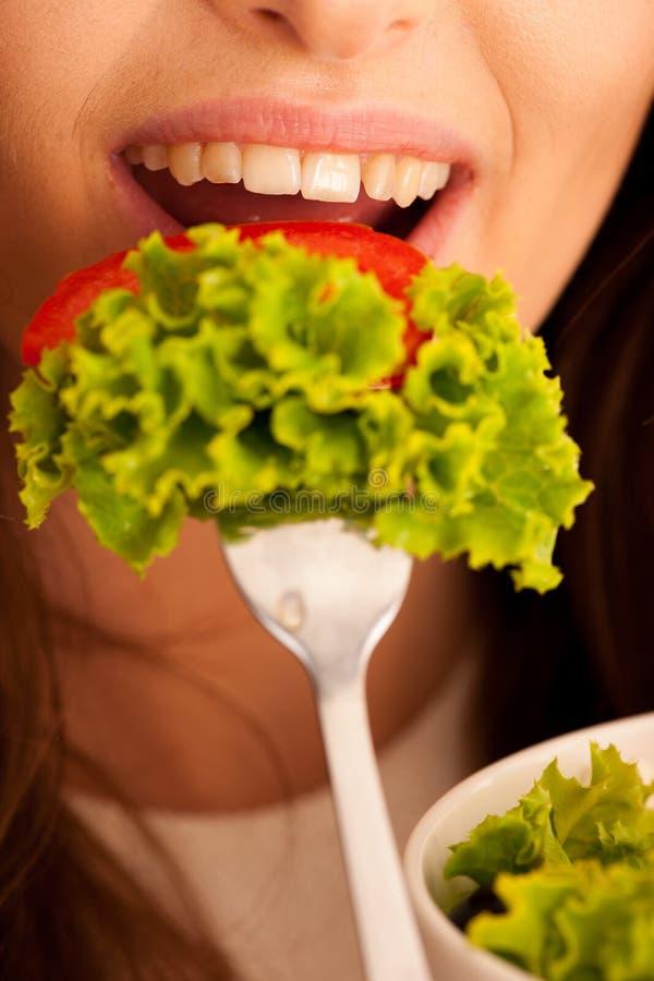 Het gezonde eten - de vrouw eet een kom Griekse over geïsoleerde salade stock afbeeldingen