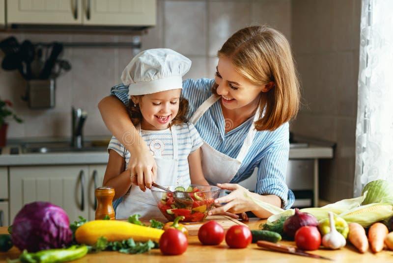 Het gezonde Eten familiemoeder en kindmeisje die vegetaria voorbereiden stock foto
