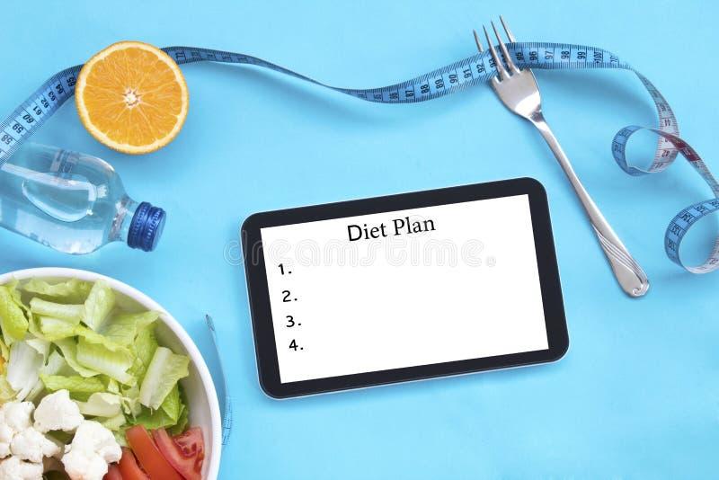 Het gezonde eten, op dieet zijn, het vermageringsdieet en wegen verliesconcept - sluit omhoog van dieetplan op het scherm van tab stock afbeelding