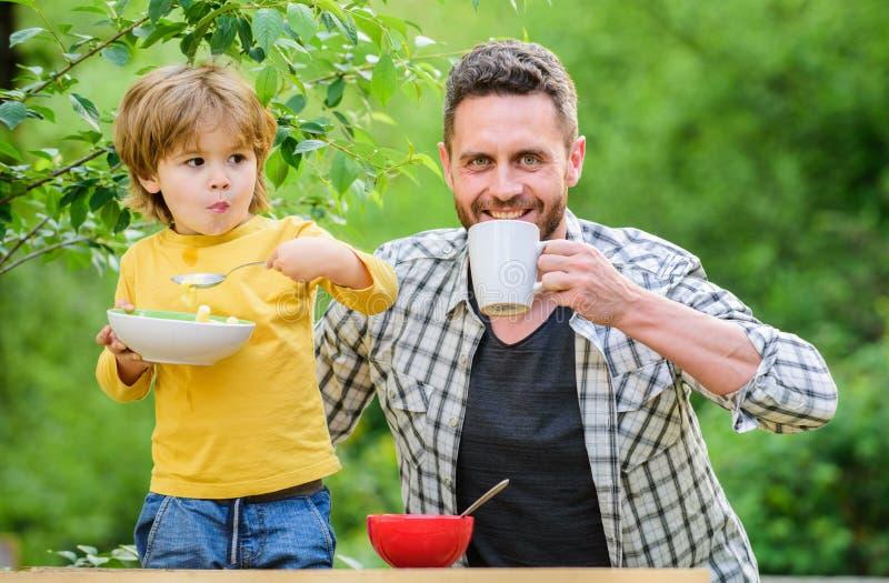 Het gezonde eten voor allebei van ons Gezond voedsel en het op dieet zijn De gelukkige Dag van Vaders Weinig jongen met papa eet  stock afbeelding