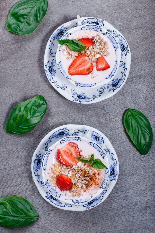 Het gezonde graangewas met aardbeien en de yoghurt verfraaien met munt in ceramische kommen op houten lijst Granola, muesli stock foto