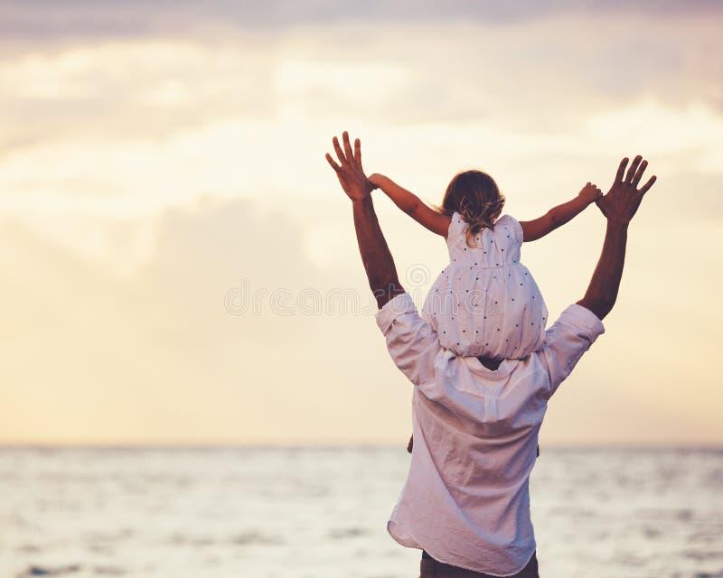 Het gezonde houdende van vader en dochter spelen samen bij het strand stock foto