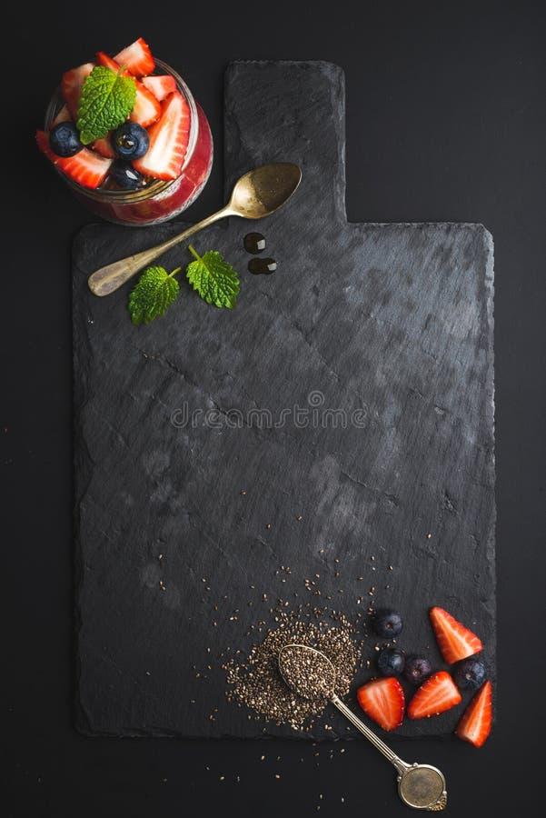 Het gezonde kader van het ontbijtvoedsel De Chiapudding met verse bessen en de munt op zwarte leisteen schepen over donkere achte royalty-vrije stock afbeeldingen