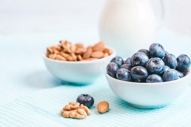 Het gezonde ontbijt, de bosbes en de melk, noten, amandel met close-up van de tekst het ruimte hoogste mening instagram filtreren stock foto