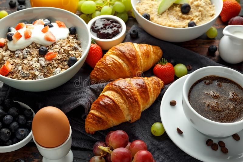 Het gezonde Ontbijt diende met koffie, jus d'orange, croissants, ei, graangewassen, havermeel en vruchten stock afbeeldingen