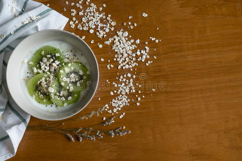 Het gezonde Ontbijt, Kom Yoghurt voegt Kiwi Fruit, Chia Seed, Haver toe stock afbeelding