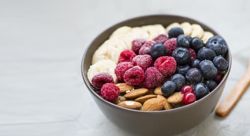 Het gezonde ontbijt met acaikom, de frambozen, de bosbessen, de amandelen, bananans, gezonde granola of muesli werpen met verse b stock foto