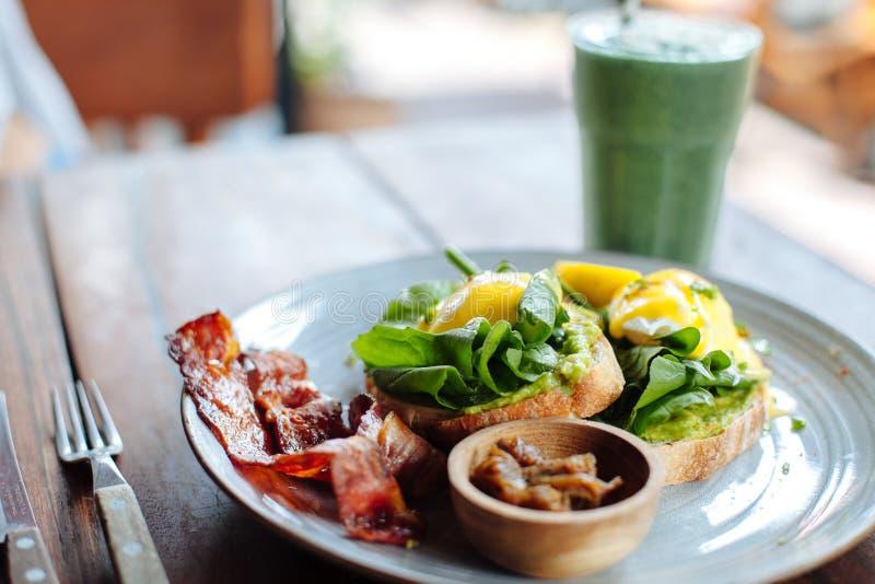 Het gezonde Ontbijt met Volkorenbroodtoost en het Gestroopte Ei met salade, avokado en wenken Groene smoothie op de achtergrond royalty-vrije stock foto