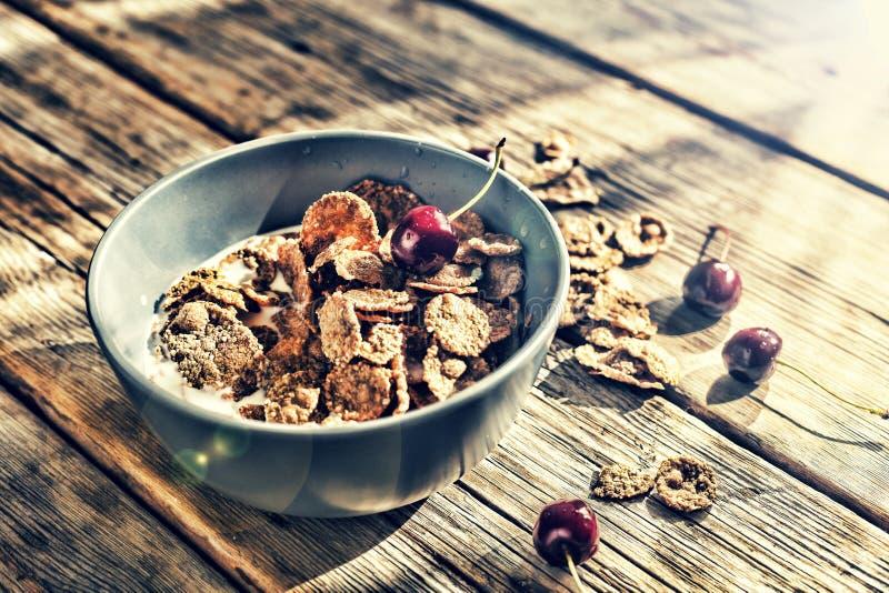 Het gezonde ontbijt schilfert met melk en verse kersen, op een houten lijst af stock foto