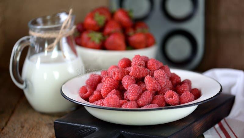Het gezonde ontbijt is verse organische frambozen, aardbeien met havervlokken en melk op een oude houten achtergrond Rustieke sti royalty-vrije stock foto