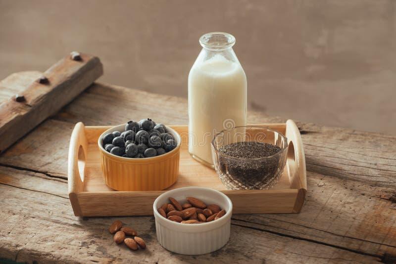 Het gezonde veganistontbijt bottelde melk met chia, amandel, vers fruit en bessen over houten lijstachtergrond, exemplaarruimte c royalty-vrije stock foto's