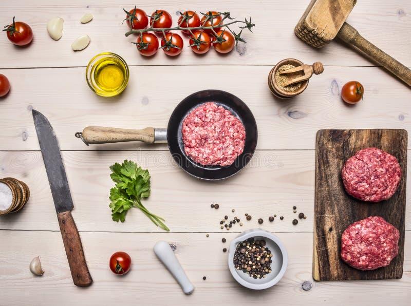 Het gezonde voedsel, het koken conceptenhuis het koken burgers, hakt in een kleine pan, kruiden, olie, keukenmes en een hamer, ee royalty-vrije stock afbeeldingen
