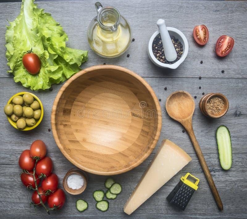 Het gezonde voedsel van de ingrediëntenvoorbereiding, sla, olijven, kersentomaten, komkommers, parmezaanse kaaskaas, rasp, specer stock afbeelding