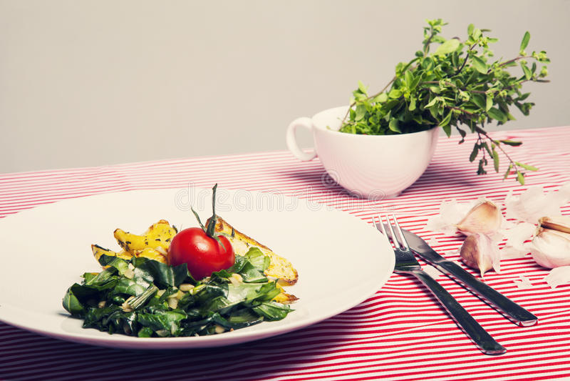 Het gezonde voedsel - vegetarische maaltijd met spinazie, aardappels en hij stock fotografie