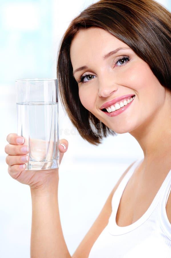 Het gezonde wijfje houdt een glas zuiver water stock afbeeldingen