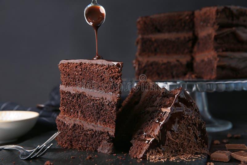 Het gieten van chocolade op stuk van smakelijke cake op lijst royalty-vrije stock foto's