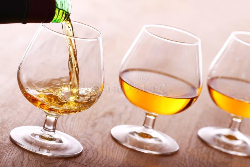 Het gieten van cognac in het glas royalty-vrije stock foto