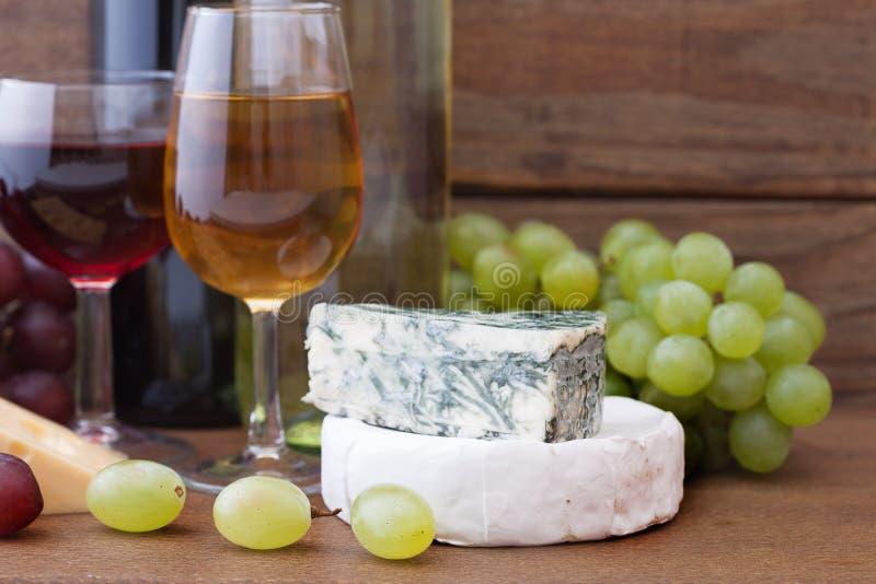 Het gieten van de wijn in wijnglas Kaas, druiven binnen stock afbeeldingen