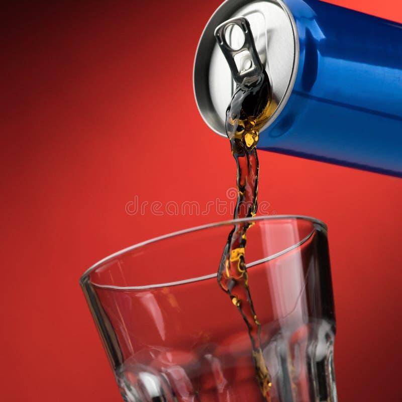 Het gieten van een frisdrank in een glas stock foto's