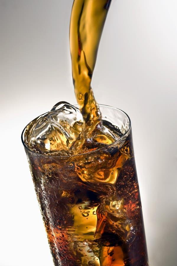 Het gieten van een glas Coca-cola met ijsblokjes royalty-vrije stock fotografie