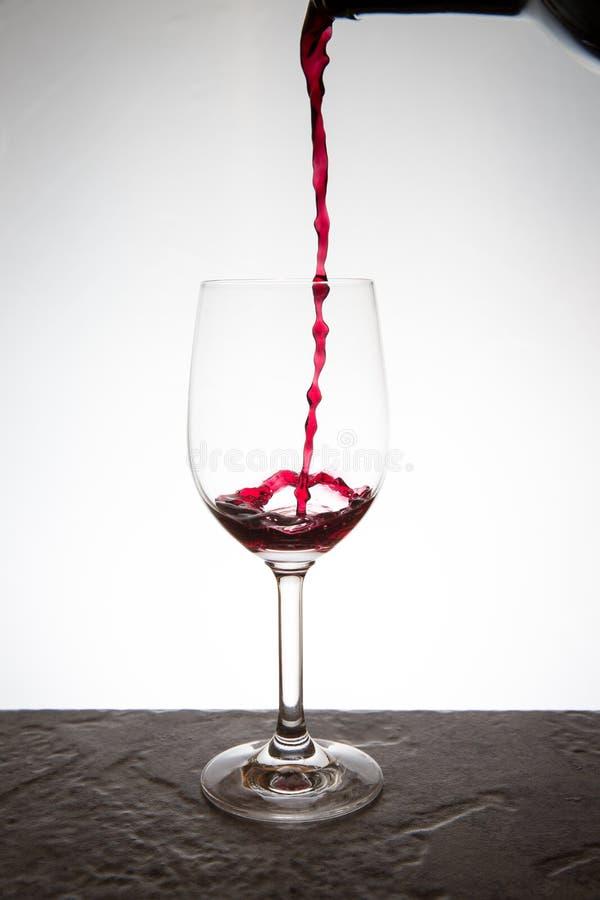 Het gieten van een glas wijn stock afbeelding