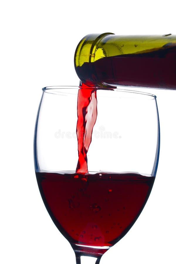 Het gieten van een rode wijn in glas stock fotografie
