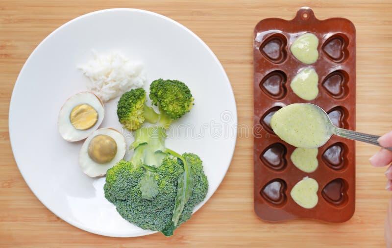 Het gieten van fijngestampt babyvoedsel in container op houten raad voor het bevriezen stock afbeeldingen