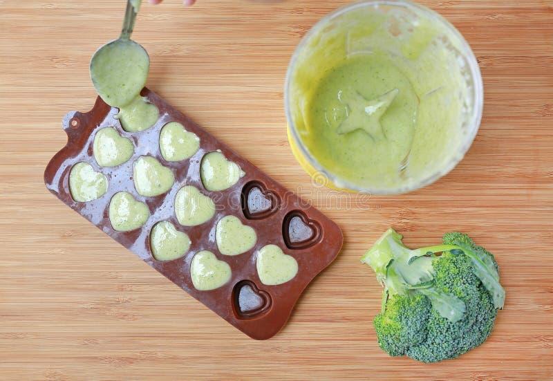 Het gieten van fijngestampt babyvoedsel in container op houten raad voor het bevriezen stock foto