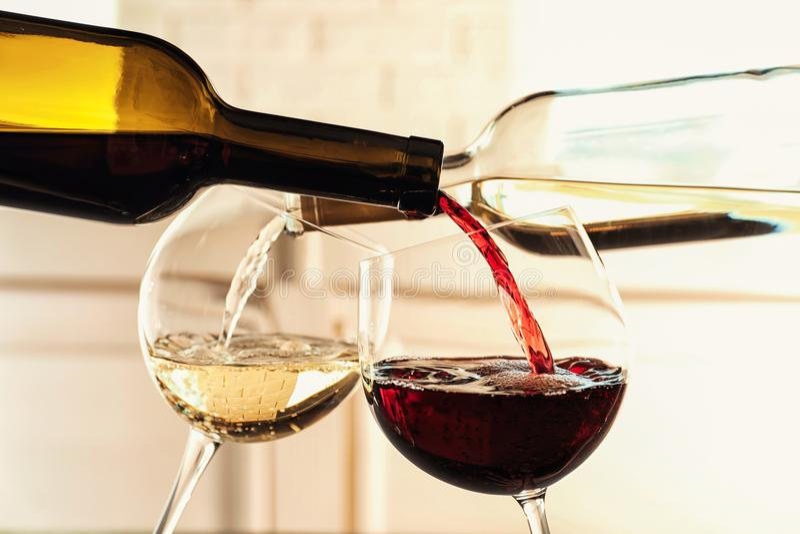 Het gieten van heerlijke wijn in glazen stock afbeeldingen