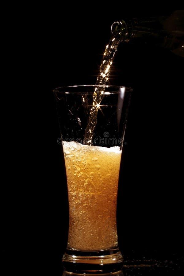 Het gieten van het bier in glas stock afbeeldingen
