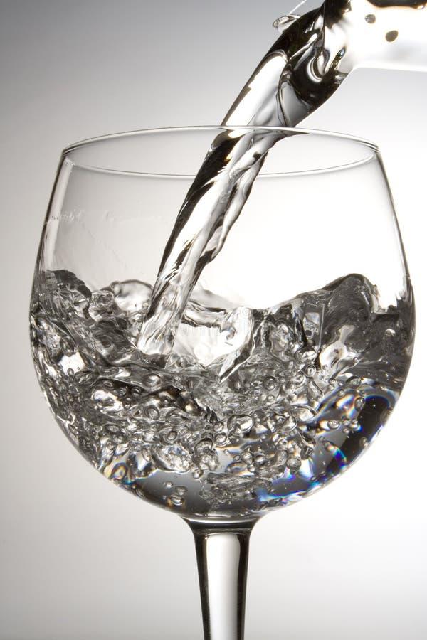 Het gieten van het water in een glas stock foto