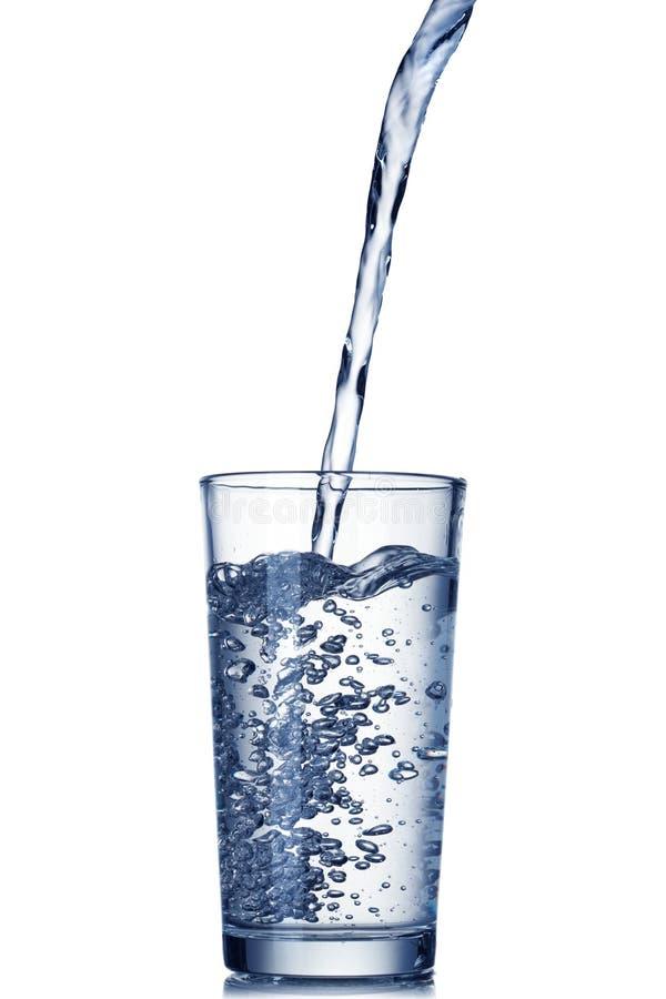 Het gieten van het water in glas op wit royalty-vrije stock afbeeldingen