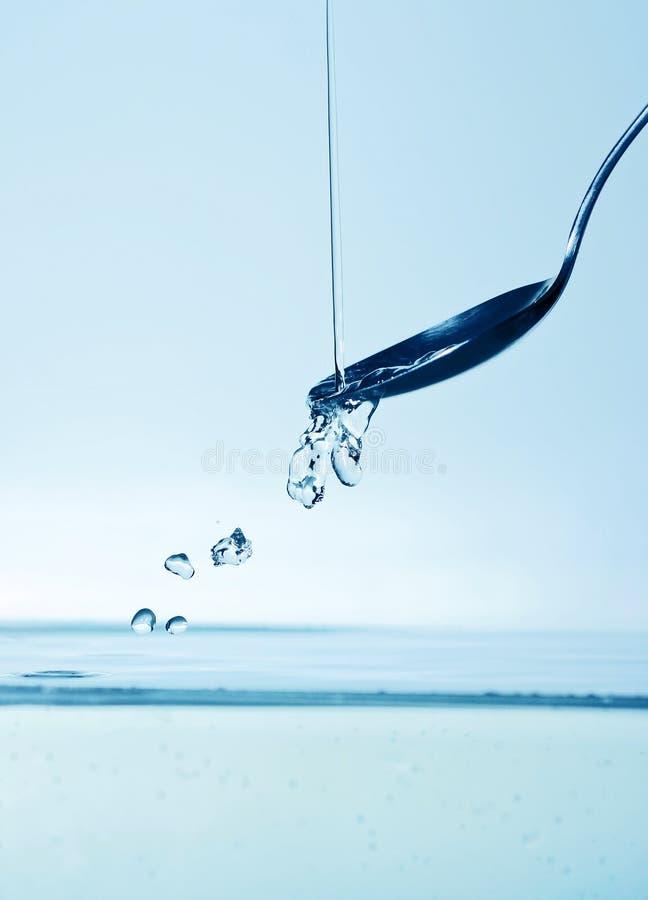 Het gieten van het water op lepel royalty-vrije stock foto
