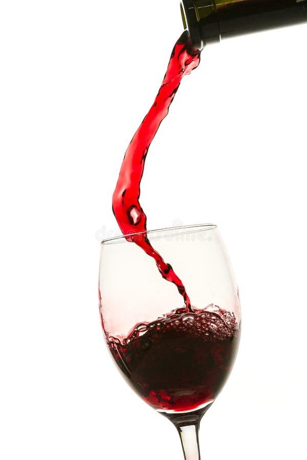 Het gieten van rode wijn in glas van fles stock afbeelding