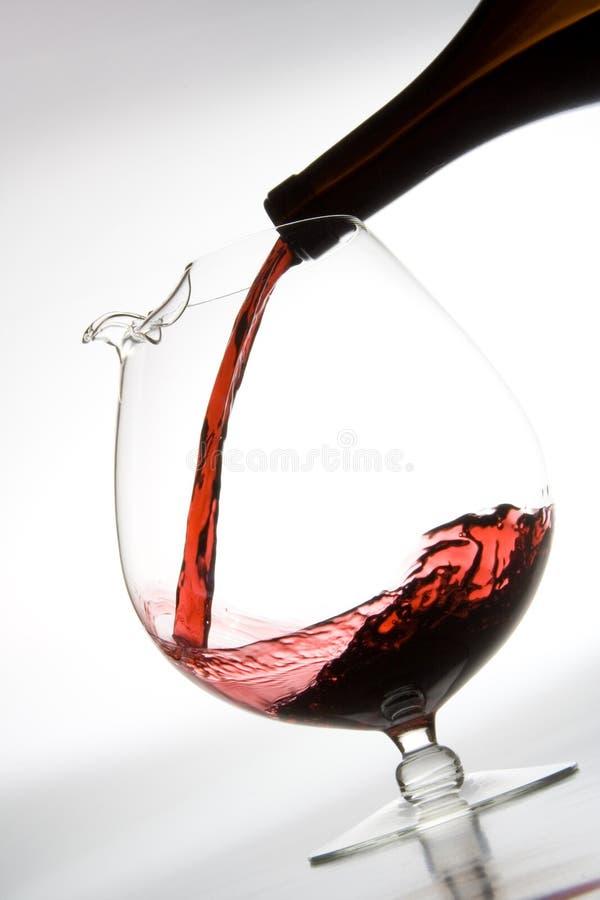 Het gieten van rode wijn in karaf stock afbeelding