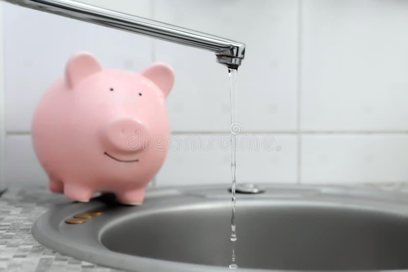 Het gieten van het spaarvarken en van het water van kraan Het concept van de waterbesparing royalty-vrije stock afbeelding