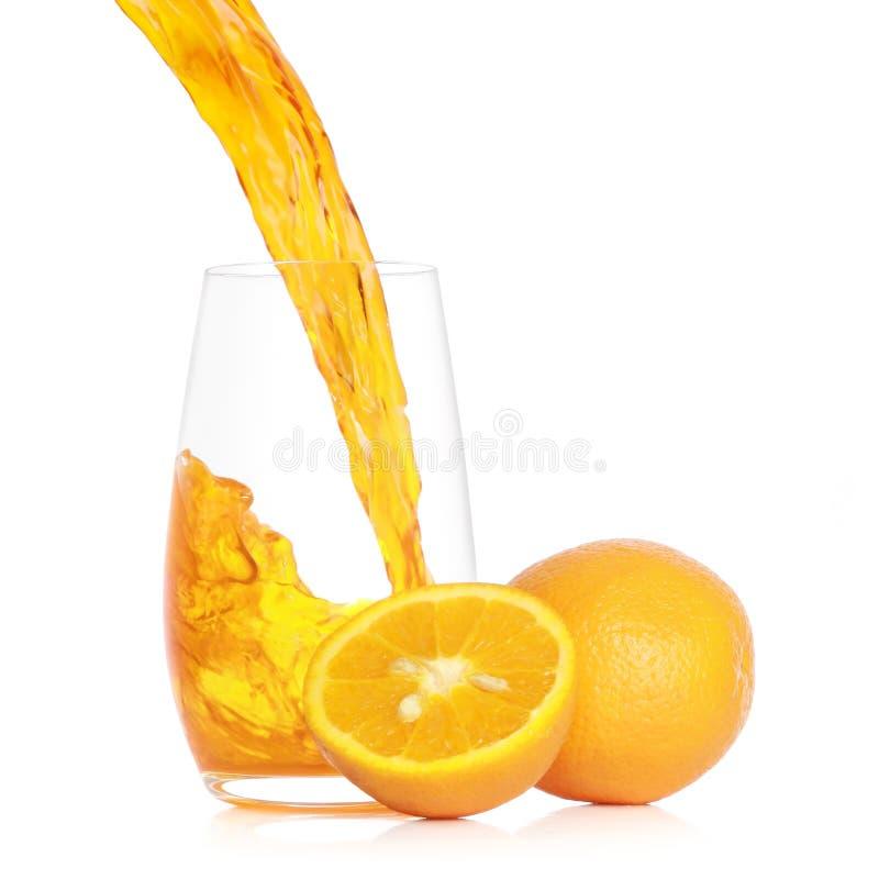 Het gieten van vers jus d'orange in een glas stock foto