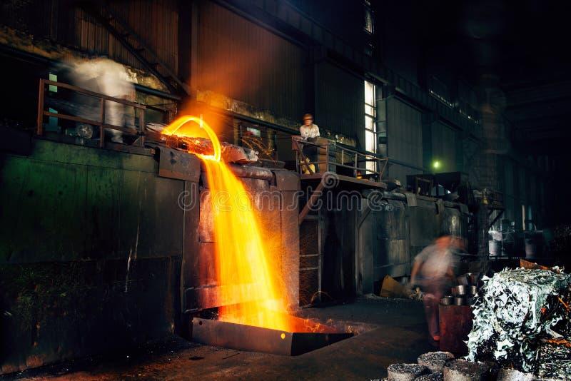 Het gieten van vloeibaar metaal in open haardworkshop royalty-vrije stock afbeelding