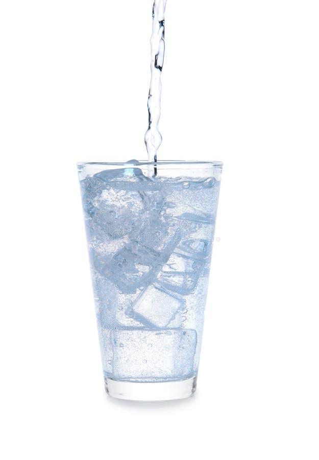 Het gieten van water in glas met ijs op witte achtergrond royalty-vrije stock fotografie