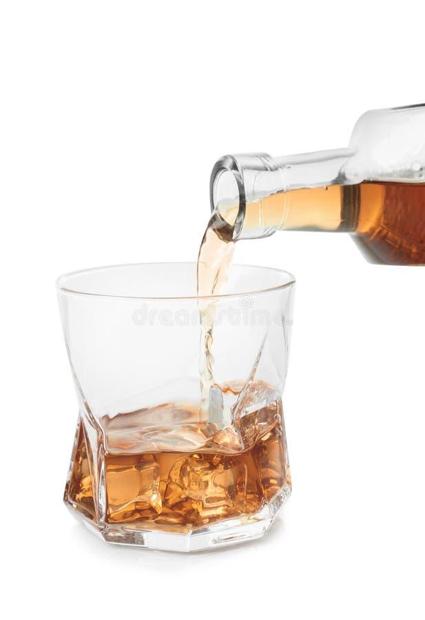 Het gieten van wisky van fles in glas op witte achtergrond royalty-vrije stock fotografie