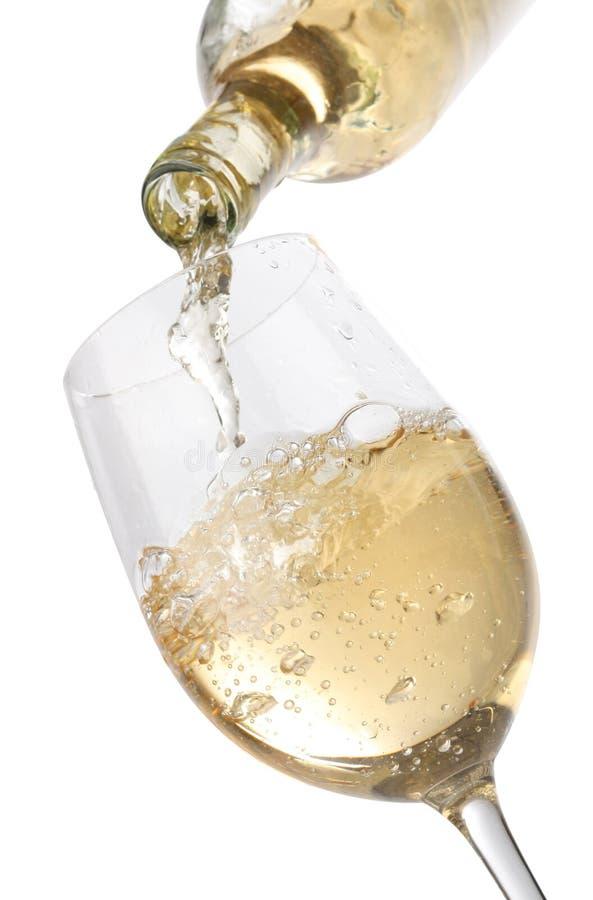 Het gieten van witte wijn in een glas stock foto's