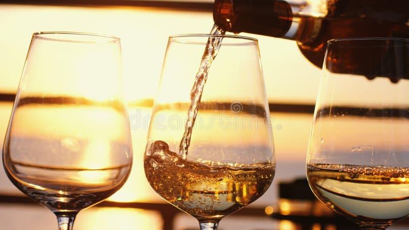 Het gieten van witte wijn in glazen bij verbazende zonsondergang door het overzees in tropische strandkoffie stock afbeelding