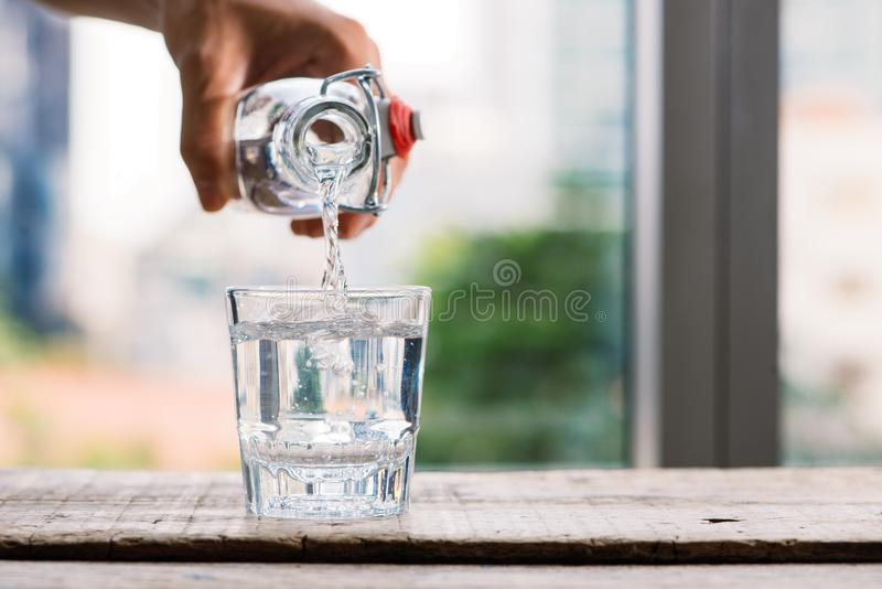 Het gieten zuiverde vers drinkt water van de fles op lijst in l stock foto's