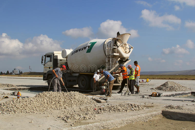 Het gietende cement van de cementvrachtwagen in een baanbouw royalty-vrije stock afbeeldingen