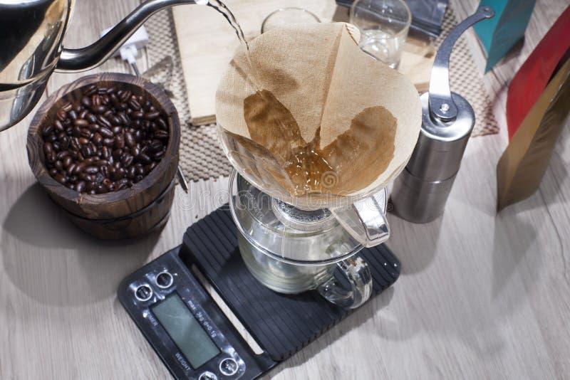 Het gietende water van de ketel aan de V60-filter die de fijngestampte koffiebonen in bevatten giet over koffiezetapparaat V60 op stock fotografie