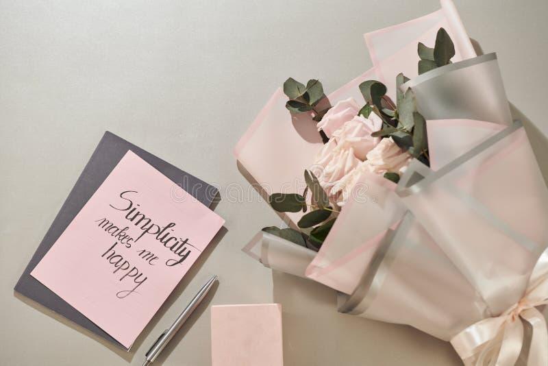 Het giftvakje, wekker en roze nam bloemen op de witte mening van de lijstbovenkant in vlakte legt stijl toe Groetkaart voor Moede royalty-vrije stock afbeeldingen