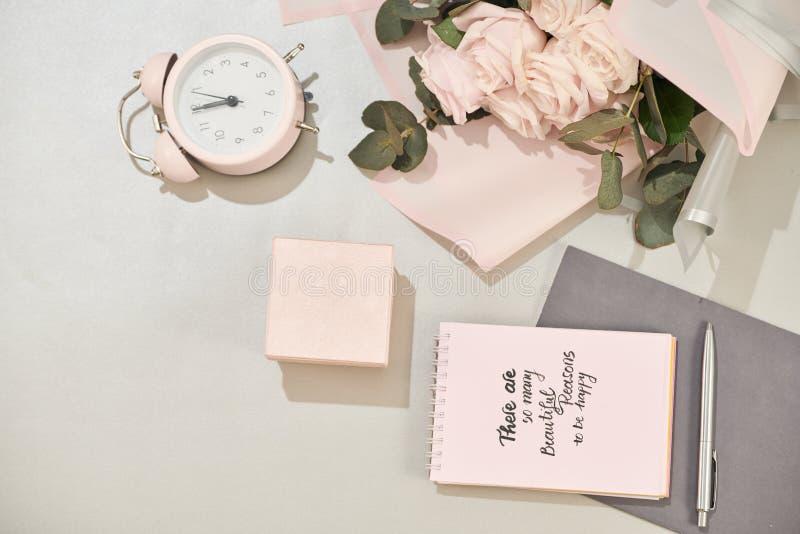 Het giftvakje, wekker en roze nam bloemen op de witte mening van de lijstbovenkant in vlakte legt stijl toe Groetkaart voor Moede stock afbeelding