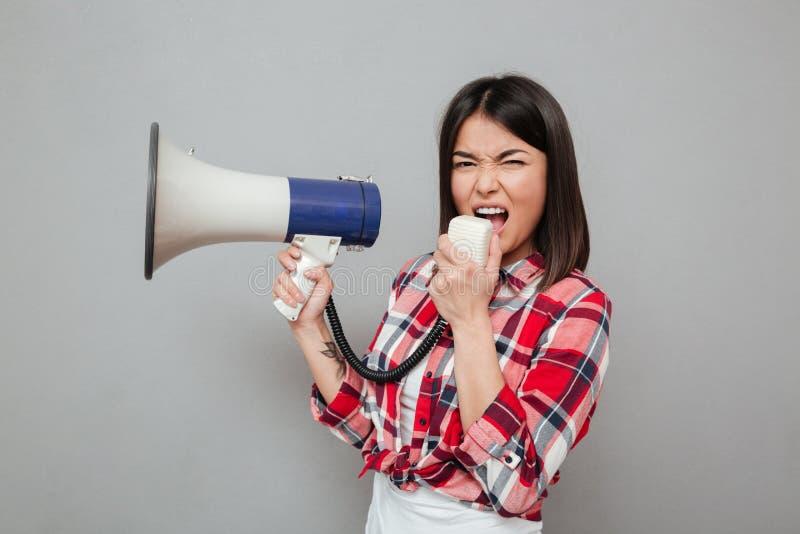 Het gillen de jonge Aziatische luidspreker van de vrouwenholding stock foto's