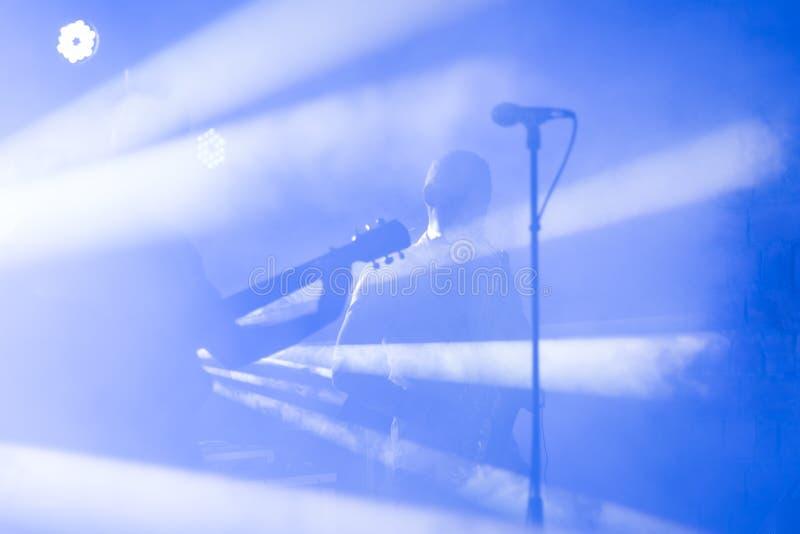 Het gitaristsilhouet presteert op een overlegstadium Abstracte muzikale achtergrond Muziekband met gitaarspeler Het spelen royalty-vrije stock afbeeldingen